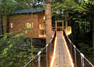 Maple View Tree House at night with cable bridge